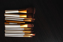 Makeup brushes gold. Makeup brushes on the table wenge dark were gold Stock Images