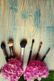 Makeup brushes and hydrangea on the abstract wooden blue backgro Royalty Free Stock Photos