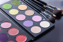 Makeup brushes and make-up eye shadows on desk Royalty Free Stock Image