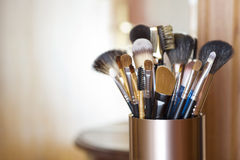 Makeup brushes in metal stand over blurred abstract room background Stock Images