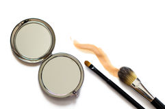 Makeup brushes an a mirror. Professional makeup brushes, a pocket mirror and foundation sample on white background Stock Image