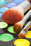 Makeup brushes and set of colorful eye shadows Stock Photos