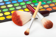 Makeup brushes and set of colorful eye shadows Royalty Free Stock Photography