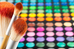 Makeup brushes and set of colorful eye shadows as background Royalty Free Stock Photos