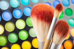 Makeup brushes and set of colorful eye shadows as background Royalty Free Stock Photo