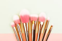 Makeup brushes on pink and mint green background stock images