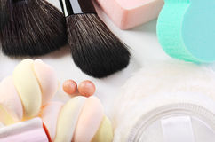 Makeup brushes, rouge balls, sponges heart shape,  powder puff a. Nd some candies on a white background horizontal Royalty Free Stock Photos