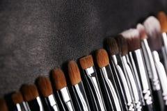 Makeup brushes set on black leather background.  Stock Photo
