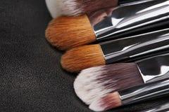 Makeup brushes set on black leather background Stock Images