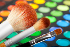Makeup brushes and colorful eye shadows Royalty Free Stock Photos