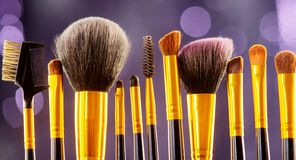 Makeup brushes set over black holiday blinking background. Various professional make up brush on dark backdrop in studio royalty free stock photography