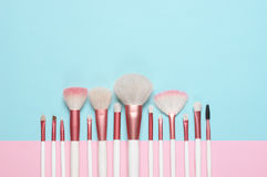 Makeup brushes set. Set of makeup brushes on pink and aqua colored composed background. Top view point, flat lay Royalty Free Stock Photo