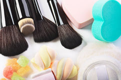 Makeup brushes, sponges heart shape,  powder puff and some candi. Es on a white background horizontal Stock Images