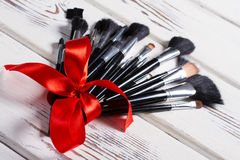 Makeup brushes tied of a red ribbon. Stock Photos