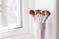 Makeup brushes in a windowsill. Makeup brushes in a pink cup on a windowsill Stock Photo