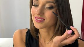 Makeup. Close Up slow motion footage of professional makeup artist applying makeup on models face before fashion show.  stock video footage