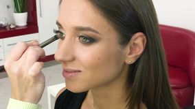 Makeup. Close Up slow motion footage of professional makeup artist applying makeup on models face before fashion show.  stock footage