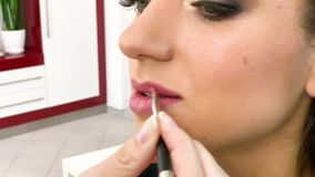 Makeup. Close Up slow motion footage of professional makeup artist applying makeup on models face before fashion show.  stock video