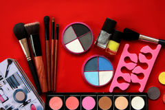 Makeup collection.Eye shadow,  brushes  on red background Royalty Free Stock Photo