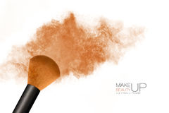 Makeup concept. Cosmetic brush with bronzing powder explosion Stock Image