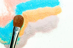 Makeup Cosmetics. Powdered and vibrant makeup colors and a cosmetics brush Stock Photo