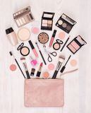 Makeup cosmetics and accessories and an open bag on white wooden background, top view stock photography