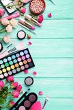 Makeup cosmetics. Different makeup cosmetics on mint wooden table royalty free stock image
