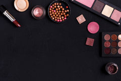 Makeup cosmetics essentials frame black background, copy space. Makeup cosmetics and other essentials frame on black background. Top view, flat lay with copy Royalty Free Stock Photos