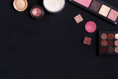 Makeup cosmetics essentials frame black background, copy space. Makeup cosmetics and other essentials frame on black background. Top view, flat lay with copy Stock Images