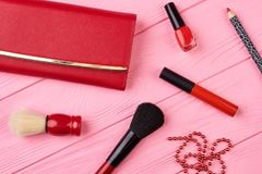 Makeup cosmetics and red purse. Set of decorative colorful cosmetics products and facial on pink wood table background. Fashion lady stylish essentials Royalty Free Stock Photos