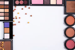 Makeup cosmetics tools and essentials frame background, copy space. Makeup cosmetics and essentials frame on white background. Top view, flat lay with copy space Royalty Free Stock Images