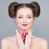 makeup De mooie Heldere Lippenstiften en de Lipgloss van de Meisjesholding royalty-vrije stock afbeeldingen