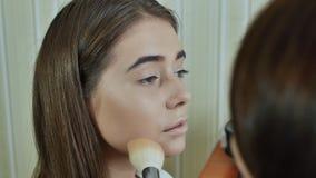 Makeup Face. Girl make-up artist treats face powder stock video footage