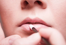 Makeup. Girl applying lipgloss lipstick on lips. Part of face. Royalty Free Stock Image