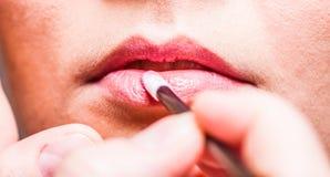 Makeup. Girl applying lipgloss lipstick on lips. Part of face. Stock Photos
