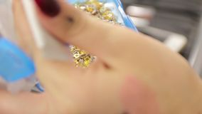 Makeup Gold Sparkles. Stars in hand female closeup in slow motion stock video footage