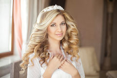 Makeup. Healthy hairstyle. Beauty bride wedding portrait. Happy. Smiling attractive girl posing at home. Bridal day preparation Stock Photography