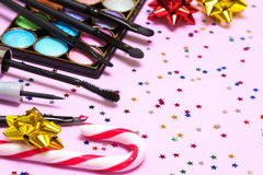 Makeup for holiday party. Red lipstick, liquid eyeliner, mascara, color glitter eyeshadow, brushes and applicator with candy cane, gift wrap bows and confetti royalty free stock photo