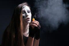 Makeup i stilen av allhelgonaaftonen En ung flicka med långt hår med målade sprickor på hennes framsida blåste ut stearinljuset S royaltyfri bild