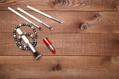 Makeup items brushes and lipstick, scattered across a wooden surface Royalty Free Stock Photos