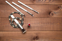 Makeup items brushes and lipstick, scattered across a wooden surface Stock Images
