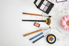Makeup items and flower on white background. Professional visage artist set royalty free stock images