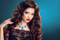 Makeup. Jewelry. Hairstyle.  Brunette woman. Beautiful girl with. Long curly hair and red lips makeup, gems expensive necklace jewelry posing on dark blue Royalty Free Stock Image