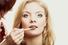 makeup Kvinna som applicerar röd läppstift med borsten Royaltyfria Foton