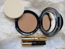 Makeup On Lace. A mirrored power compact with a sponge, lipstick and a mini mascara on a background of lace Stock Photography