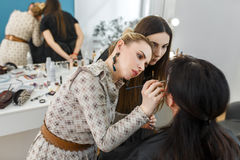 Makeup lesson at beauty school. Professional makeup teacher with her student girl. Makeup tutorial lesson at beauty school. Make-up artist work in her studio Stock Photo