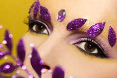 Makeup. Makeup with lilac and yellow shadows in the eyes of the girl with shiny leaves on a yellow background Stock Photography