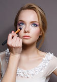 Makeup. Make-up Applying closeup. Cosmetic Powder Brush for Make up. Perfect Skin. Nude Lipstick.  on a rey Royalty Free Stock Photos
