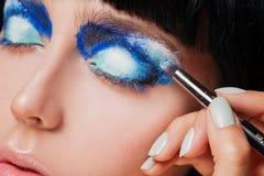Makeup. Make-up. Painting blue eyeshadows. Eye Stock Image