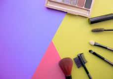 Makeup and makeup brushes, eye shadows on a colored background. Cosmetics for the face. With empty space on the left royalty free stock images